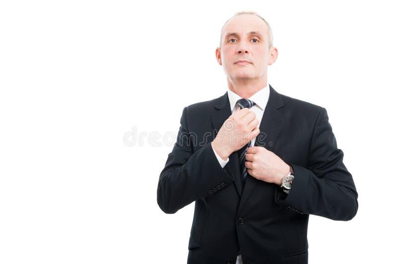 Middenleeftijds elegante mens die zijn band aanpassen die kostuum dragen royalty-vrije stock foto's