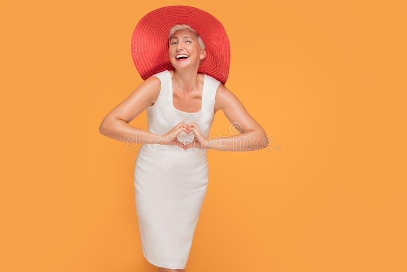 Middenleeftijds glimlachende vrouw in rode de zomerhoed stock foto
