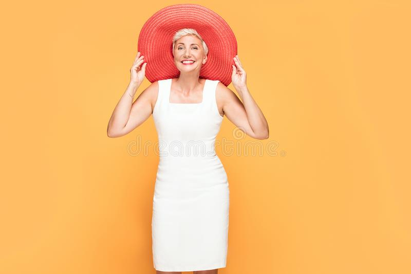 Middenleeftijds glimlachende vrouw in rode de zomerhoed stock foto's