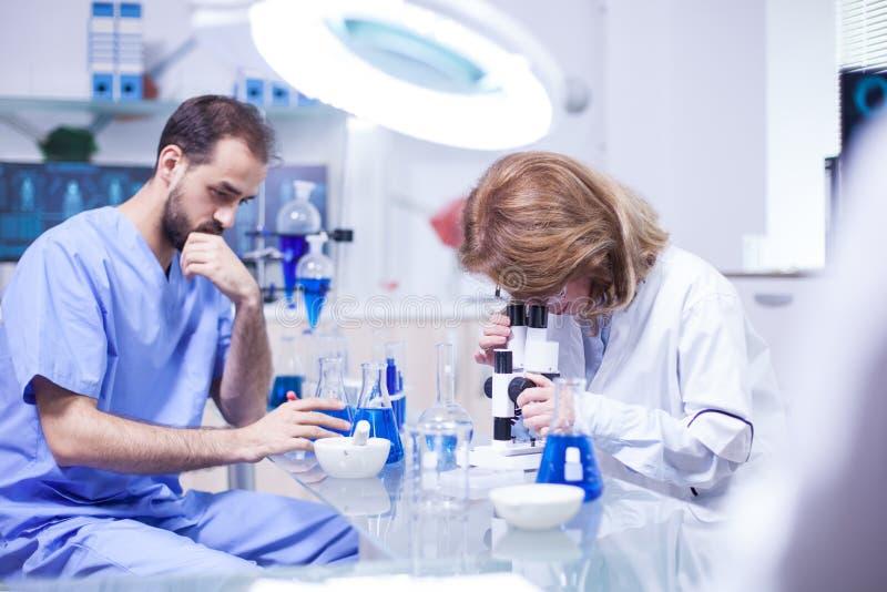 Middenleeftijds vrouwelijke wetenschapper die met microscoop in laboratorium werken stock afbeelding