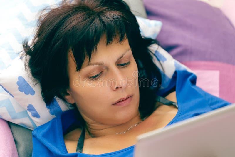 Middenleeftijdsvrouw die in bed met tablet rusten stock foto's
