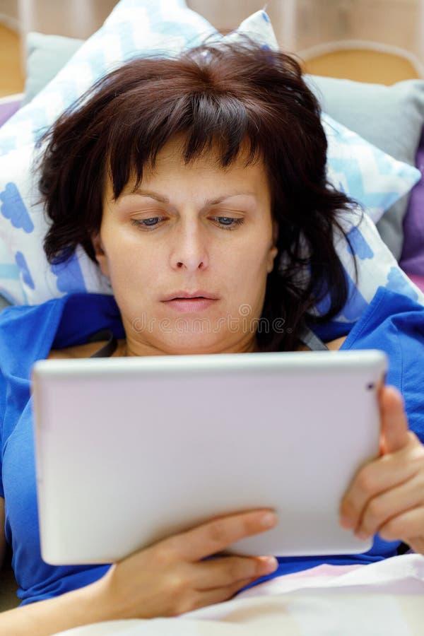 Middenleeftijdsvrouw die in bed met tablet rusten stock afbeelding
