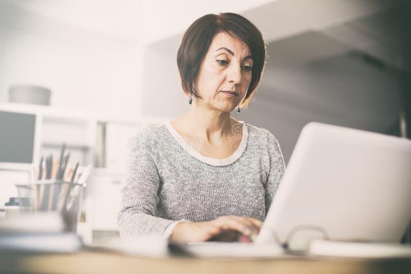 Middenleeftijdsvrouw die computerpt gebruiken royalty-vrije stock afbeeldingen