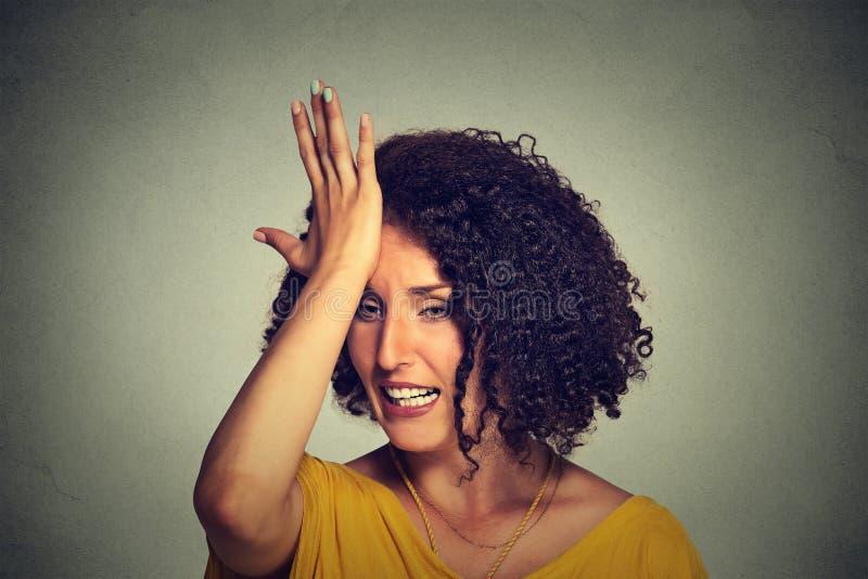 Middenleeftijdsvrouw die hand op hoofd meppen om duh gemaakte fout te zeggen stock foto's