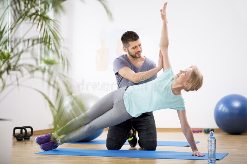 Middenleeftijdsvrouw die op blauwe mat tijdens fysiotherapie met jonge mannelijke arts uitoefenen royalty-vrije stock afbeeldingen