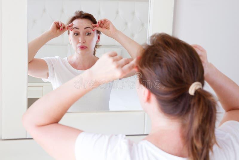 Middenleeftijdsvrouw die in spiegel op het voorhoofd van de gezichtsrimpel in slaapkamer kijken Rimpels en het anti het veroudere royalty-vrije stock foto