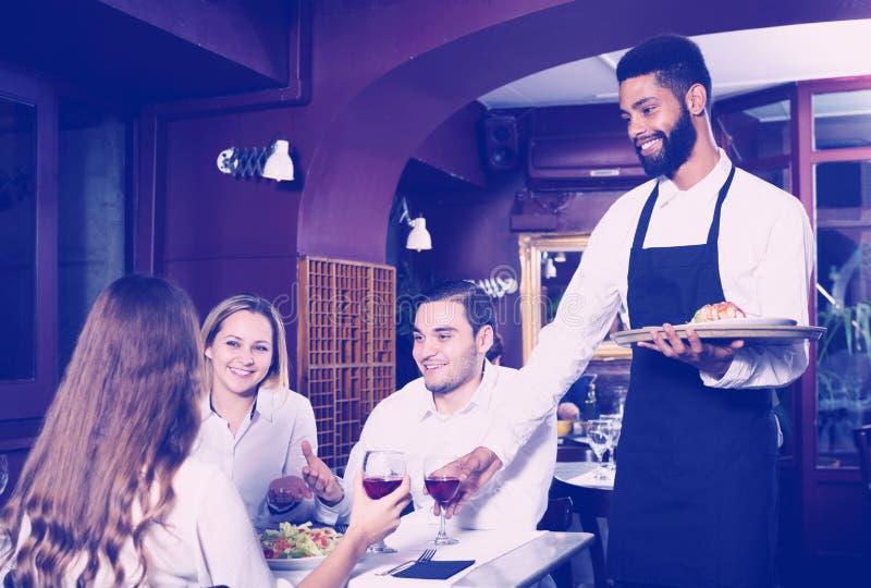 Middenstandrestaurant en vrolijke kelner stock afbeelding