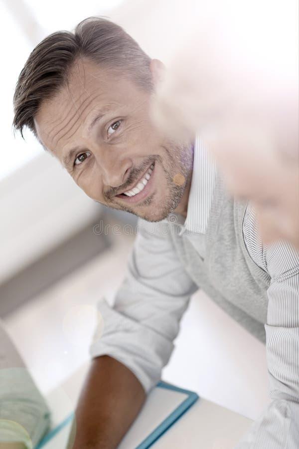 Middke-åldras stilig man som ler på kontoret royaltyfri fotografi