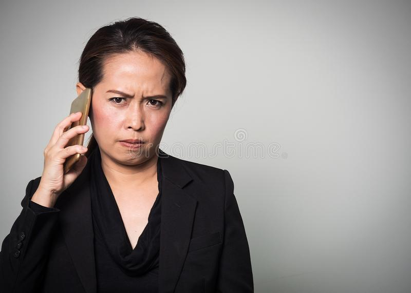 Middle adult Asian woman holding smart phone in angry and boring. Emotion. Portrait on white background. Studio shot royalty free stock images