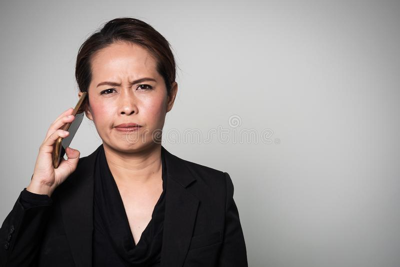 Middle adult Asian woman used smart phone. Action boring and take away from ear. Portrait on white background with copy space royalty free stock photos