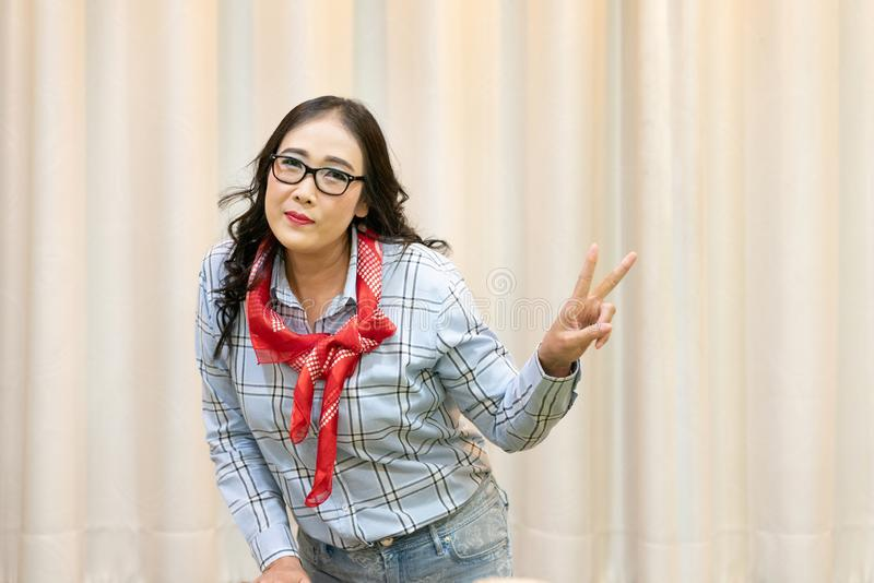 Middle adulthood long black hair Glasses woman wearing plaid shirt with cowboy bandana on Curtain background. Attractive cowgirl in checkered shirt with blank royalty free stock image