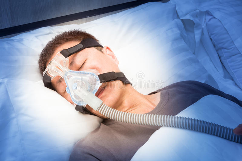 middle age asian man sleeping in his bed wearing CPAP mask connecting to air hose, device for people with sleep apnea stock photography