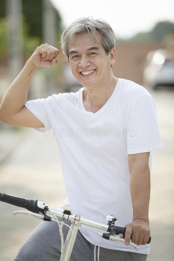 Middle age asian man toothy smiling face happiness emotion exercise by riding bicycle in home village street stock photos