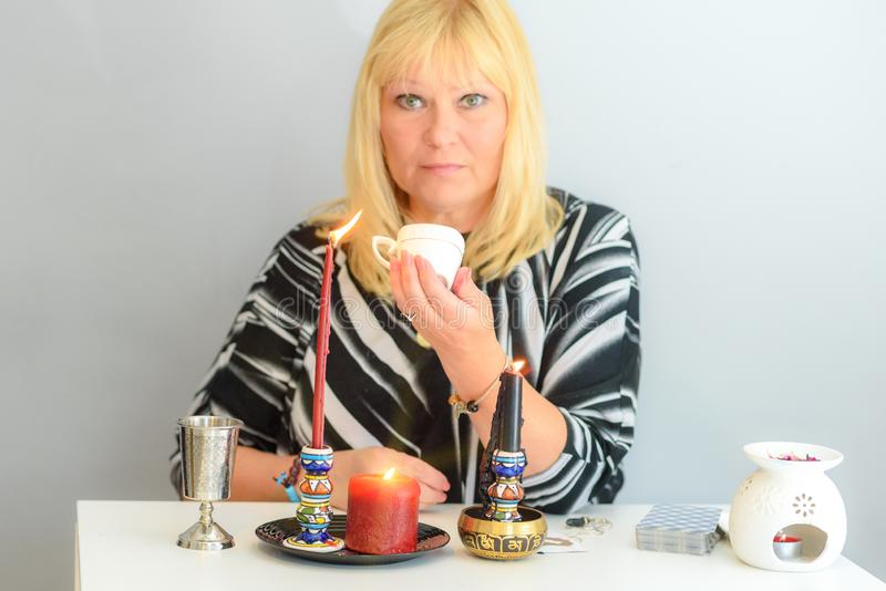 Portrait of beautiful middle age woman sits near a fortune teller desk with a tarot cards and candles. Middle age beautiful woman guessing on the coffee grounds royalty free stock image