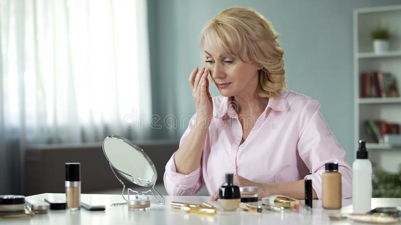 Middle-age blond lady applying anti-wrinkle cream on face in front of mirror royalty free stock image
