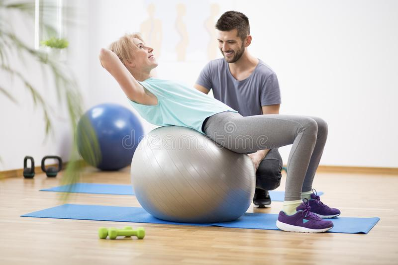 Middle age blond woman exercising on gymnastic ball during session with physiotherapist. Middle age blond women exercising on ball during session with stock photography