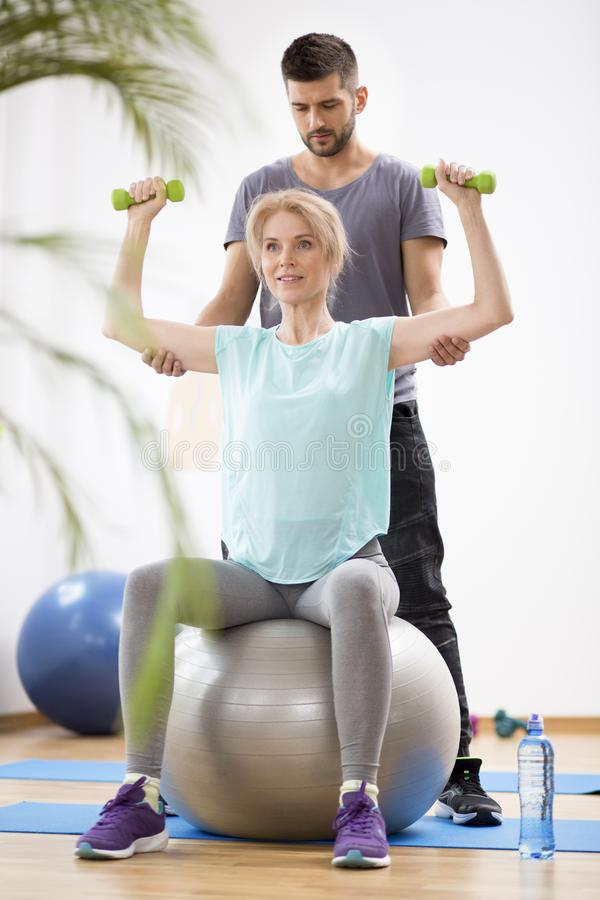 Middle age blond woman exercising on gymnastic ball during session with physiotherapist. Middle age blond women exercising on gymnastic ball during session royalty free stock images