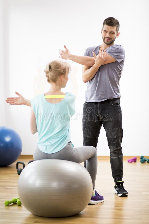 Middle age woman exercising on gymnastic ball during session with physiotherapist. Middle age blond women exercising on gymnastic ball during session with stock photos