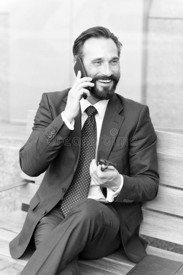 Middle age businessman sitting on bench using his cell phone. Smiling bearded businessman sitting on bench and talking phone-. Calling in city business center royalty free stock photo