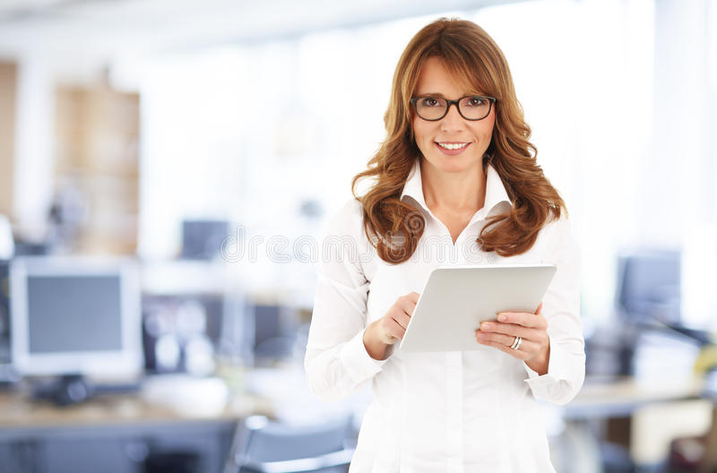 Middle age businesswoman with digital tablet. Portrait of middle age businesswoman holding digital tablet and standing at office royalty free stock photography