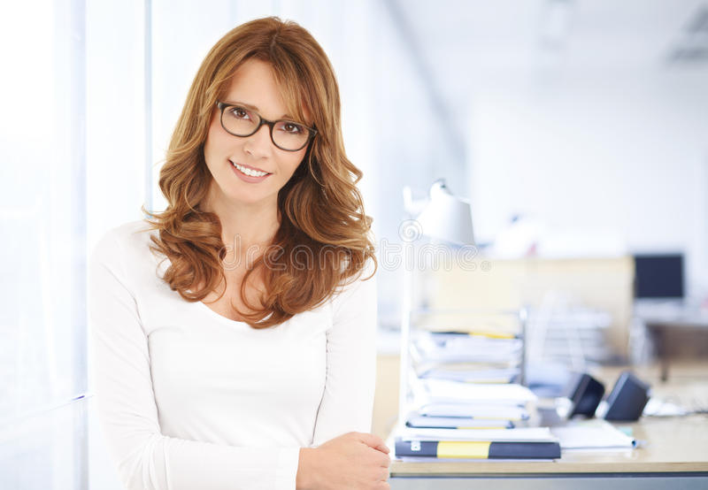 Middle age businesswoman portrait. Executive middle age businesswoman standing at office. Business people stock photo