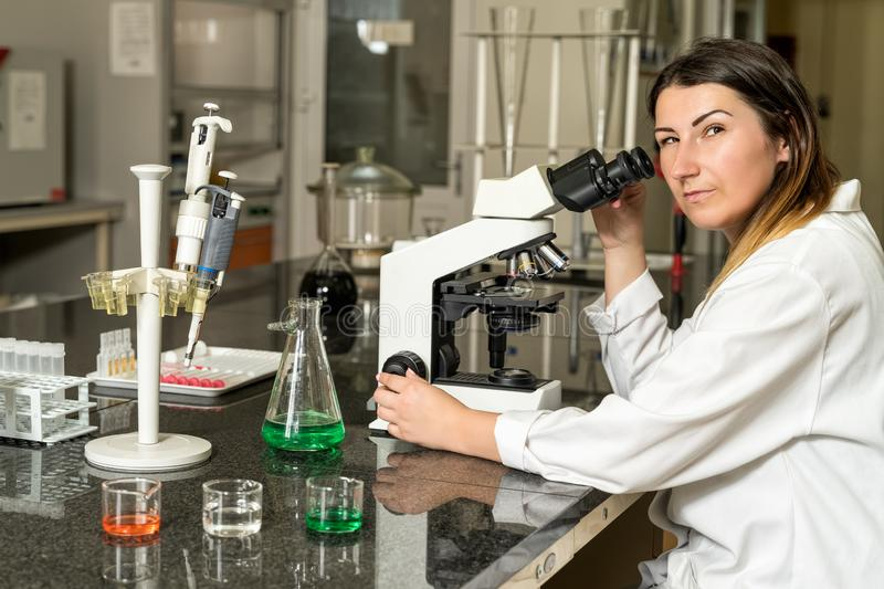 Middle age female laboratory technician sitting next to compound microscope royalty free stock image