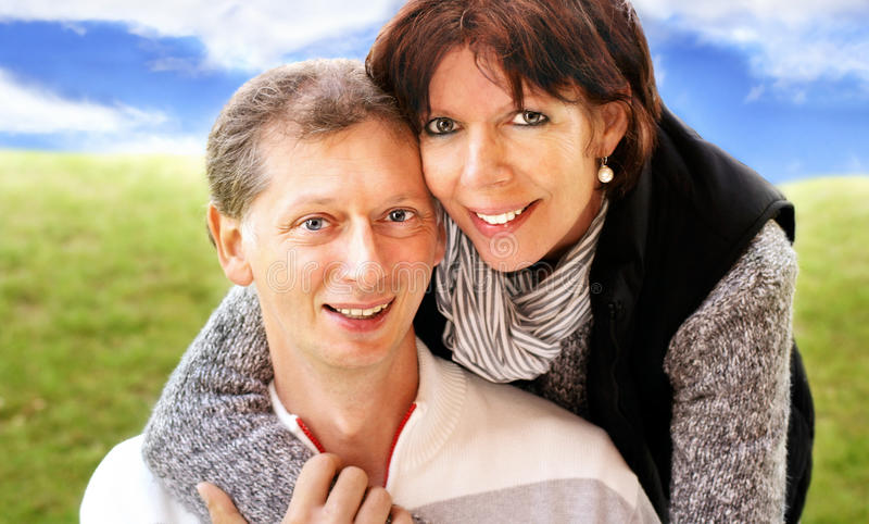 Middle-age couple embraced outdoor. Sympathetically middle-age couple embraced, outdoor with grass and sky background stock image