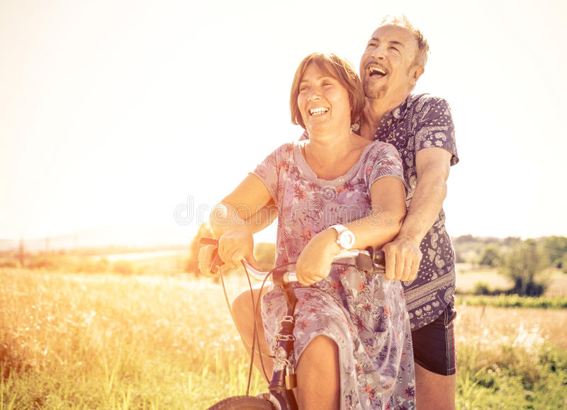 Middle age couple going for a ride with the bicycle stock images