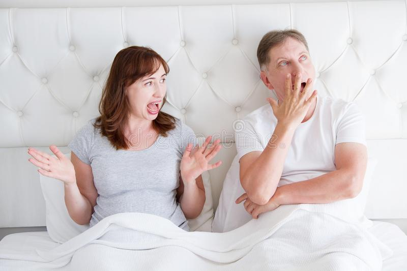 Middle age couple with quarrel problem in relationship in bed. Family life. Copy space. Boring and sleepy yawn concept royalty free stock photo