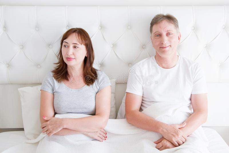Middle age couple with quarrel problem in relationship in bed. Family life. Blank t shirt. Copy space royalty free stock photos