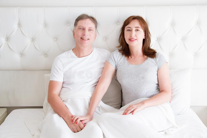 Middle age couple with wrinkles sitting in bed. Template blank t shirt. Woman and man in bedroom. Healthy lifestyle and sleep royalty free stock photography