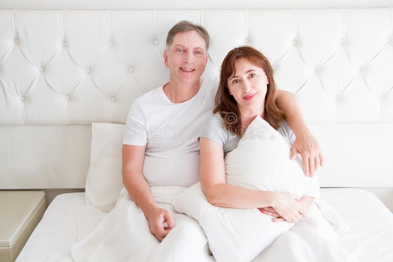 Middle age couple with wrinkles sitting in bed. Template blank t shirt. Woman and man in bedroom. Healthy lifestyle and sleep stock photos