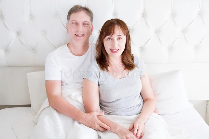 Middle age couple with wrinkles sitting in bed. Template blank t shirt. Woman and man in bedroom with perfect white teeth. Healthy. Middle age couple with royalty free stock image