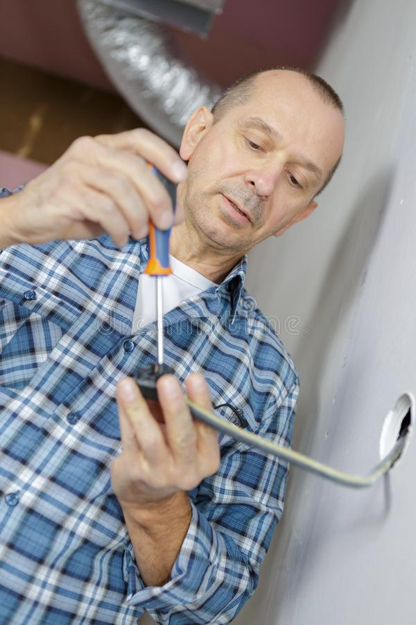 Middle-age electrician hands fixing socket royalty free stock images