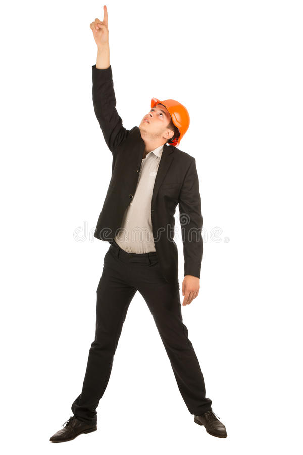 Middle Age Engineer in Orange Helmet Pointing Up. Middle Age Male Engineer in Orange Helmet Wearing Black Coat and Pants Pointing Up. Isolated on Full White stock image