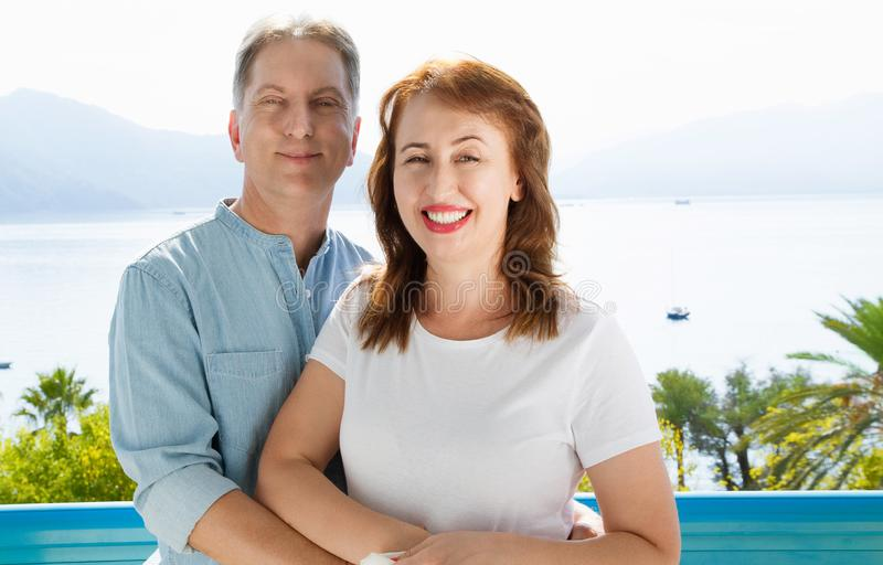 Middle age family couple on vacation resort on sea background. Summer people travel to tropical beach. Summertime leisure royalty free stock images