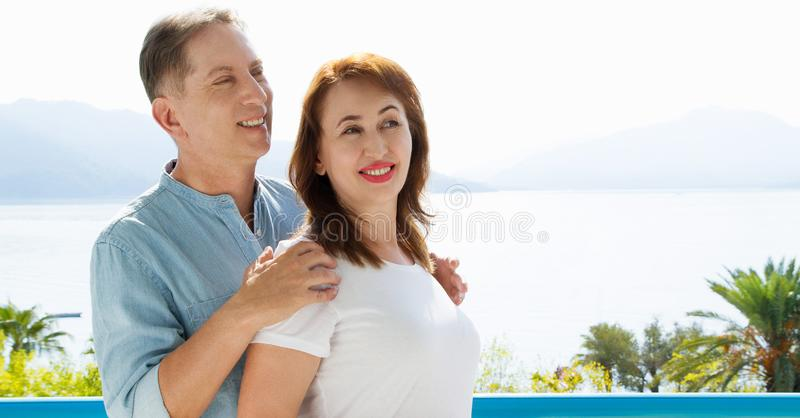 Middle age family couple on vacation resort on sea background. Summer people travel to tropical beach. Summertime leisure royalty free stock photos