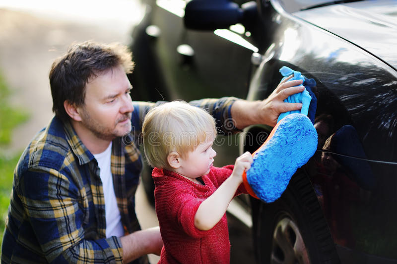 Middle age father with his toddler son washing car together outdoors royalty free stock photography