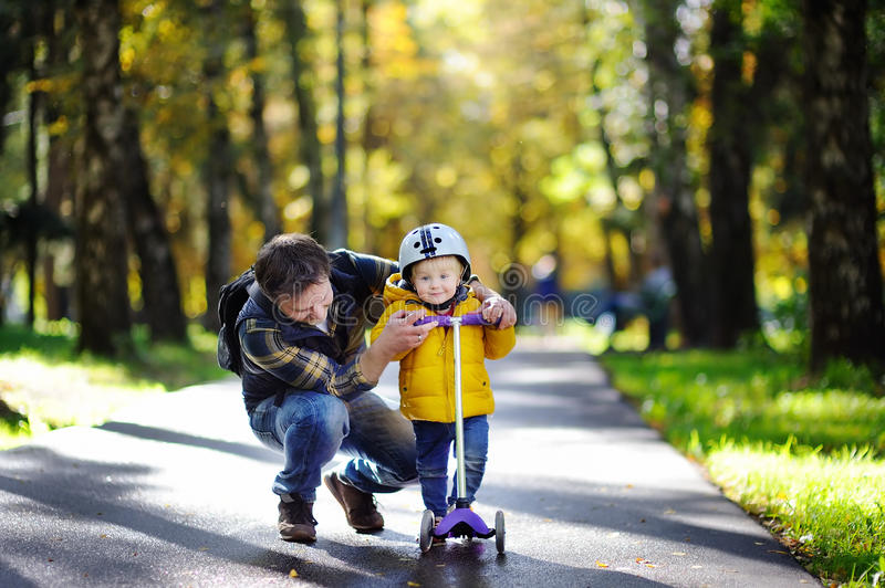 Middle age father showing his toddler son how to ride a scooter in a autumn park. Active family leisure. Child in helmet. Safety, sports, leisure with kids stock photography