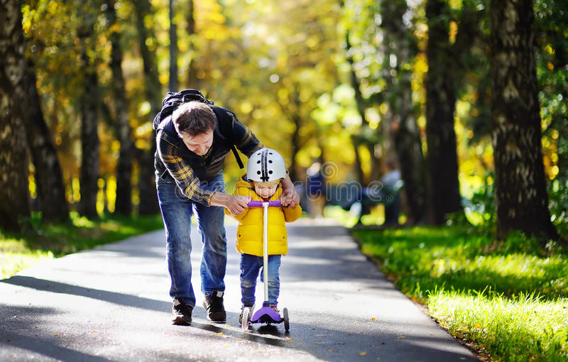 Middle age father showing his toddler son how to ride a scooter in a autumn park. Active family leisure. Child in helmet. Safety, sports, leisure with kids royalty free stock image