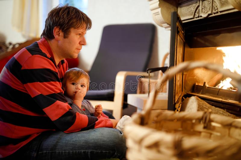 Middle age father sitting by fireplace with cute little baby girl at home. Happy family, dad with daughter make fire for stock image