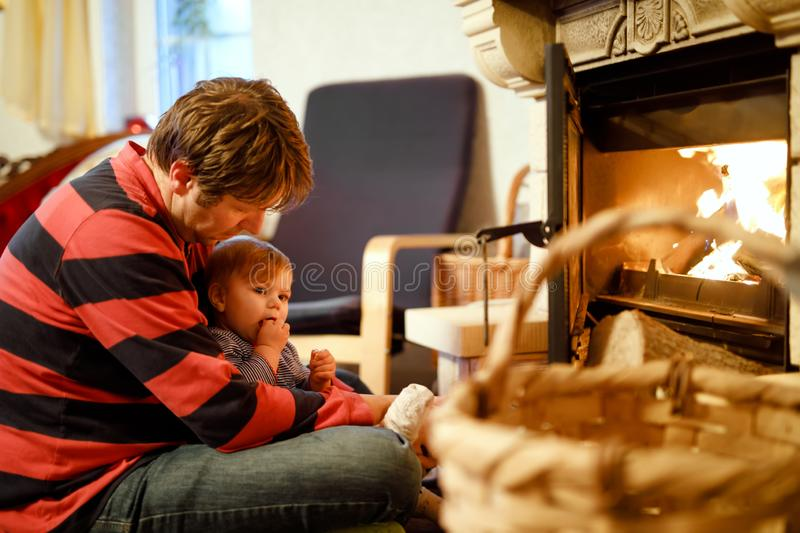 Middle age father sitting by fireplace with cute little baby girl at home. Happy family, dad with daughter make fire for stock images