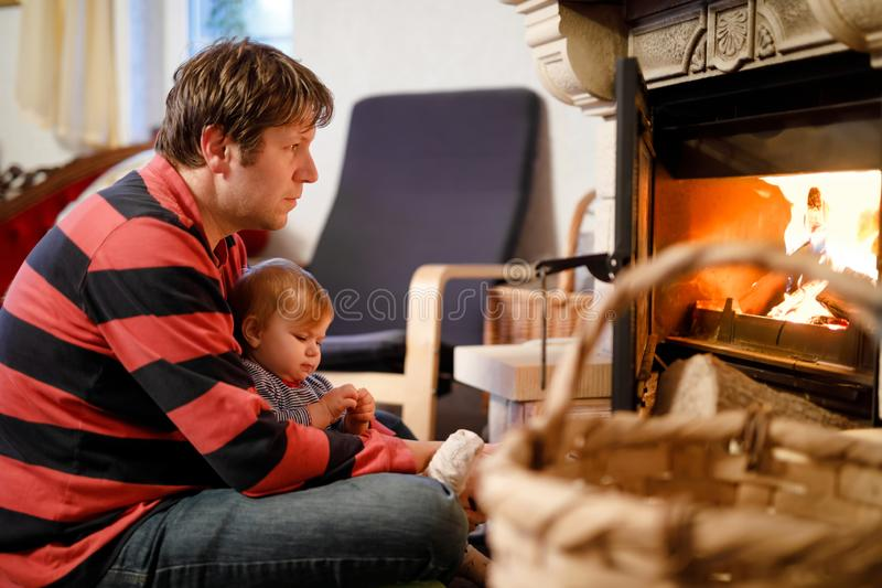 Middle age father sitting by fireplace with cute little baby girl at home. Happy family, dad with daughter make fire for royalty free stock image