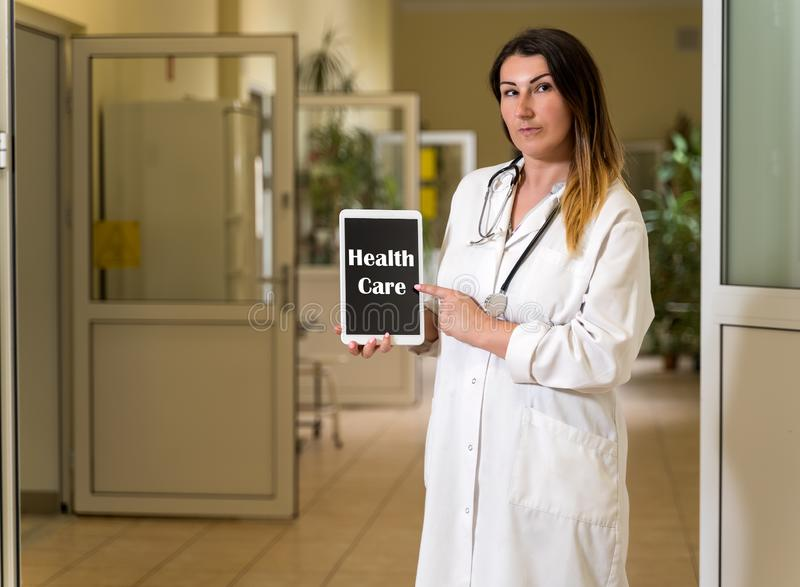 Middle age female doctor in white robe holding and pointing to tablet with Health Care text. Middle age, Caucasian white, female doctor in white robe with stock photo