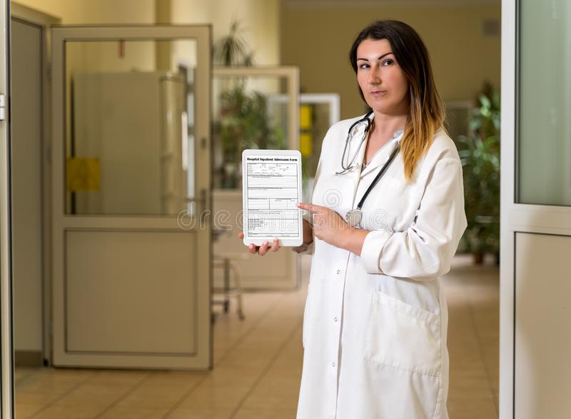 Middle age female doctor in white robe holding and pointing to tablet with Hospital Admission form stock image