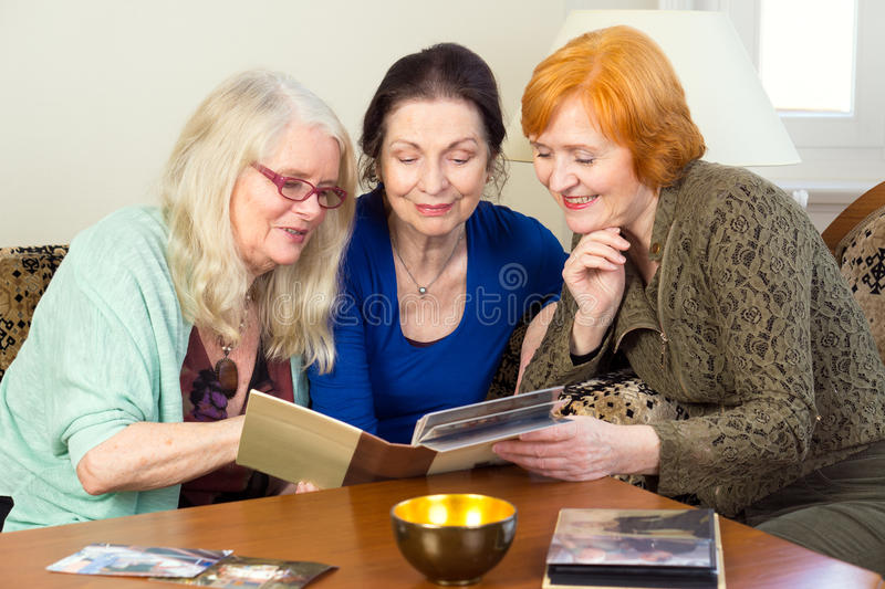 Middle Age Female Friends Looking at Photo Album. Close up Three Middle Age Female Friends Sitting at the Living Area Looking at Photo Album Together and Talking royalty free stock images