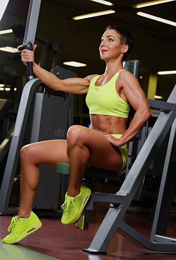 Middle age female posing on fitness exercise machine. stock photo