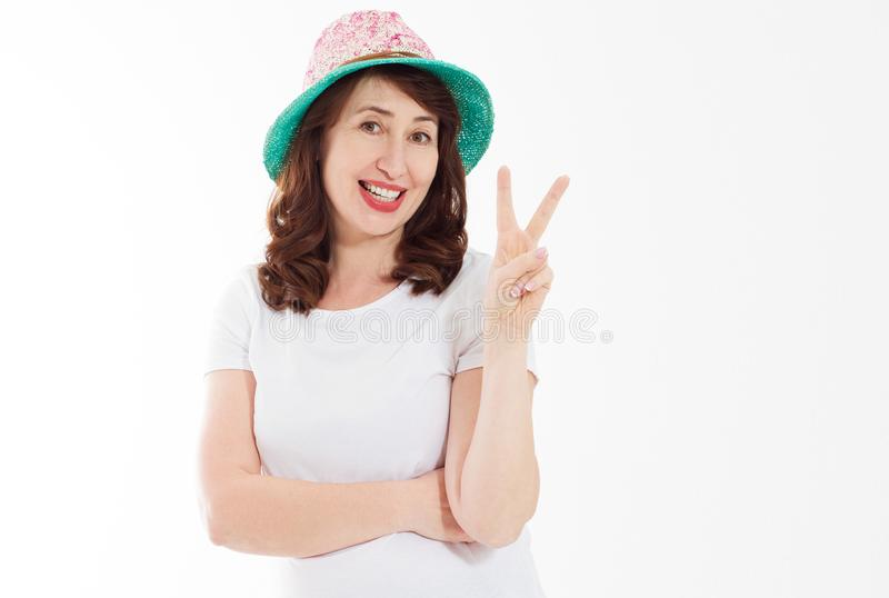 Middle age happy face woman showing victory peace sign isolated on white background. Female in beach hat and template t shirt royalty free stock images