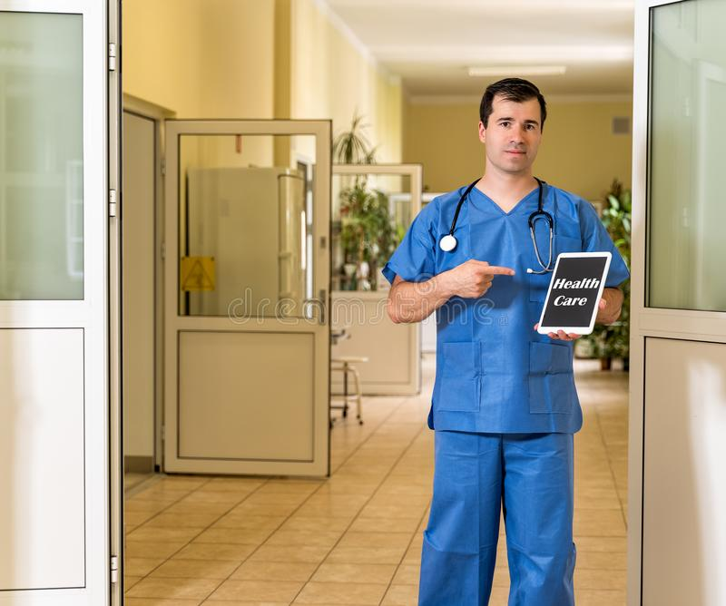 Middle age male doctor in blue scrubs holding and pointing to tablet with Health Care text royalty free stock images