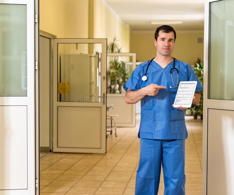 Middle age male doctor in blue scrubs holding and pointing to tablet with Hospital Admission form royalty free stock images